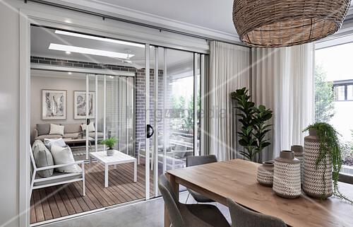 Esszimmer mit Holztisch, Blick durch geöffnete Glastür auf Terrasse