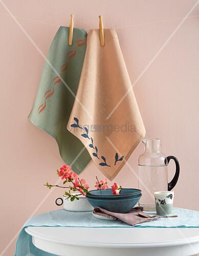 Bedruckte Geschirrtücher hängen an der Leine vor rosafarbener Wand