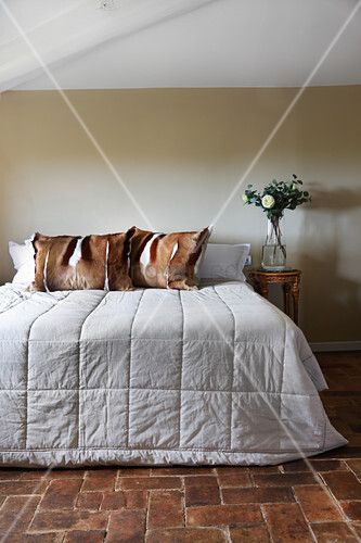 Fur pillows on bed on rustic brick floor