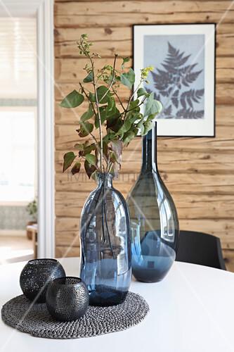 Blaue Glasvasen und schwarze Windlichter auf dem Tisch
