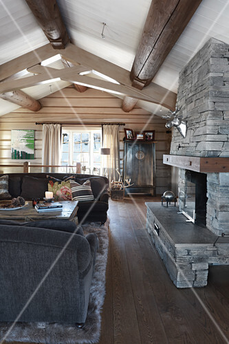 Open fireplace and exposed ceiling beams in rustic living room