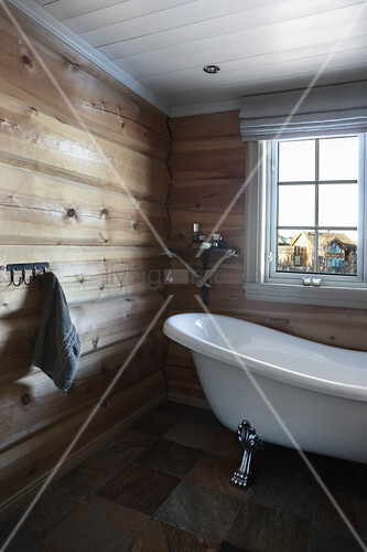 Wooden walls and free-standing bathtub in rustic bathroom