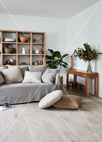 Sofa with grey loose cover and scatter cushions in front of wooden shelving in living room
