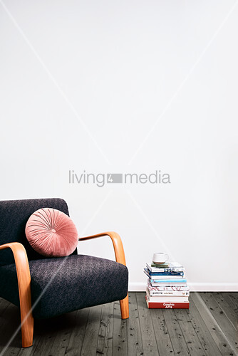 Stack of books used as side table next to retro armchair with round velvet cushion
