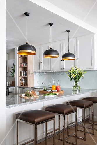 Breakfast bar, bar stools and black designer lamps in white kitchen