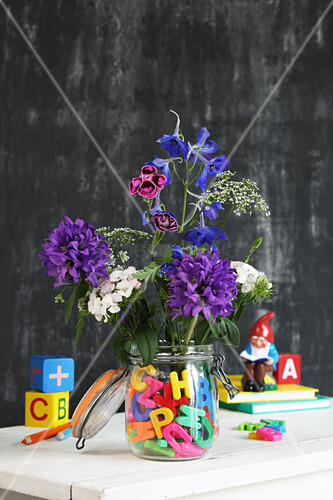 Flowers in preserving jar of water and colourful letters