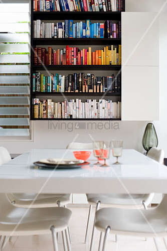 View of bookcase across white dining table