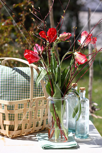 Bouquet of tulips and branches on garden table