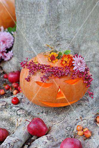 Carved pumpkin, wreath of pepper and shrub verbenas