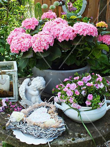Hydrangea, angel statue, mini petunias, vine heart and candle lantern