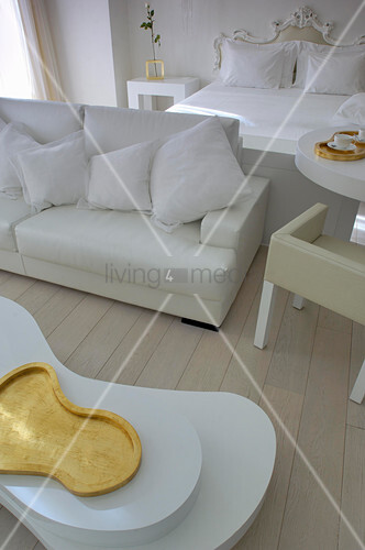 Double bed, couch and coffee table with organic shape in white room