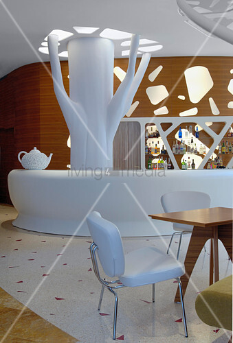 White bar and tree-like sculpture in hotel lobby