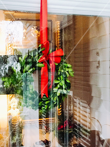 Festive wreath with red ribbon hung behind window