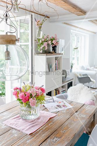 Sommerstrauß auf Esstisch, im Hintergrund Wohnzimmer im Shabby Style