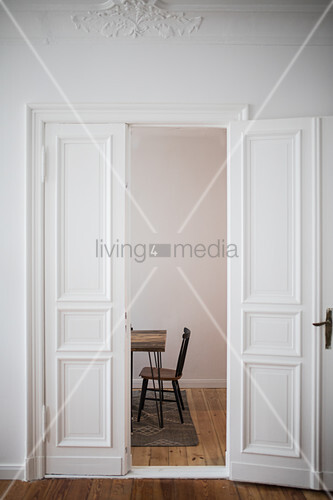 Open panelled doors in period apartment with view of chair and table