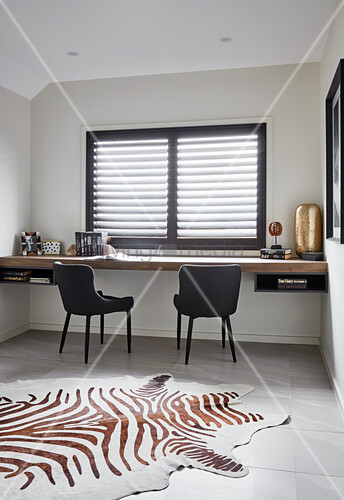 Floating wooden desk, black chairs and zebra-skin rug in study