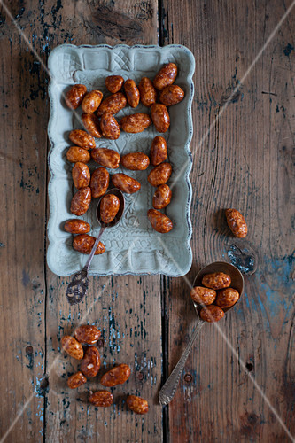Caramelised nuts on blue plate and wooden table
