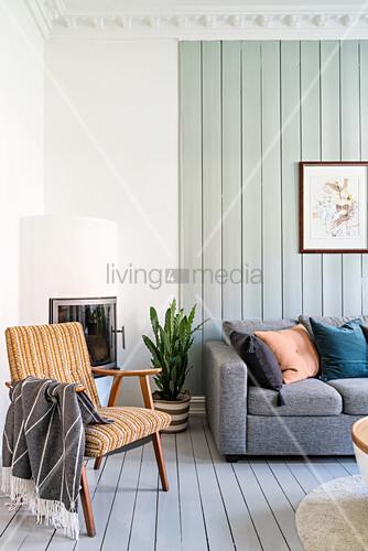 Retro Armlehnstuhl vor Kamin und graue Sofagarnitur im Wohnzimmer mit hellgrün gestrichener Holzwand