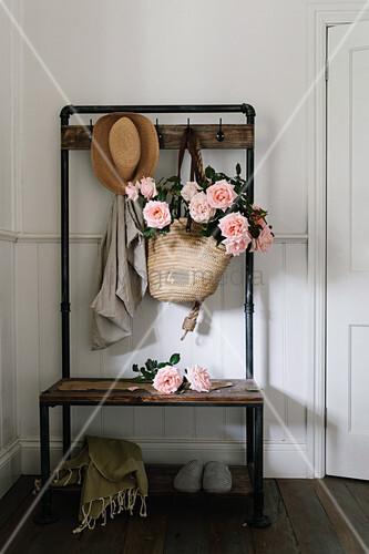 Korbtasche mit Teerosen an Vintage Garderobe