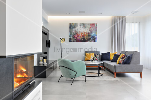 Upholstered furniture in elegant lounge and fireplace in foreground of open-plan interior