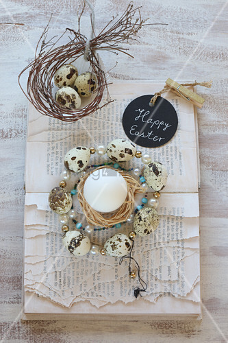 Wreath of beads and quail eggs on book with torn pages