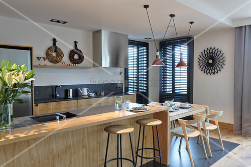 Kitchen counter with bar stools and breakfast table at one end