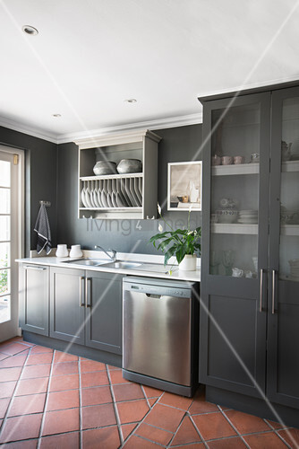 Grey kitchen counter with glass-fronted cupboards and plate rack