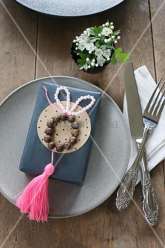 Osterhase aus Perlen mit pinker Quaste auf einem Geschenk
