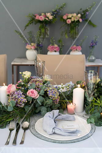 Festively decorated table with lavish floral garland as centrepiece