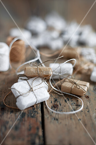 Small gifts wrapped in white and pale brown on wood