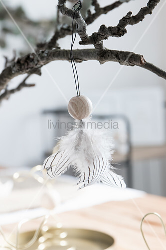 Angel handcrafted from wooden bead and feathers hung from gnarled branch