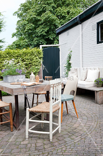 Rustic wooden table and chairs on paved terrace