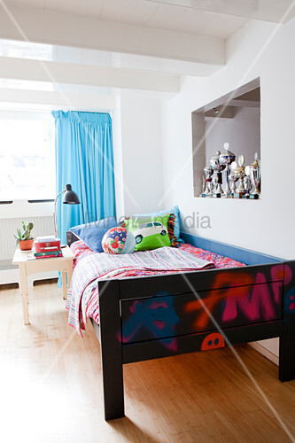 Wooden bed with colourful bed linen, row … – Buy image ...