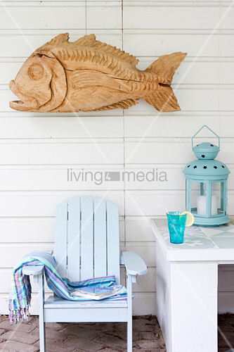 Wooden sculpture of fish on board wall above pale blue deckchair