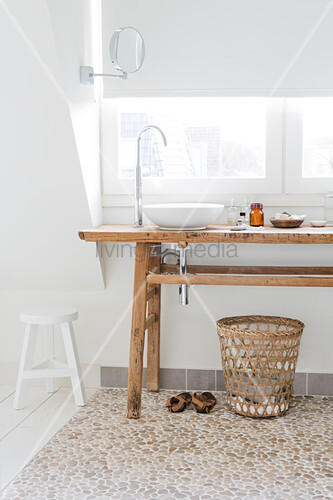 Twin sinks on rustic wooden table in white bathroom