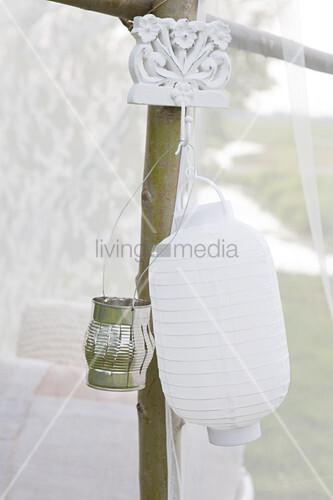 Weiße Laterne und Windlicht im Garten aufgehängt