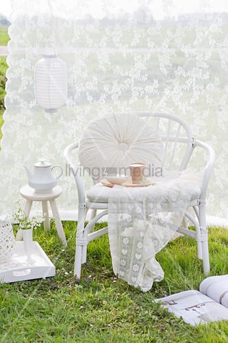 Gemütlicher Rattansessel vor weißem Vorhang im Garten