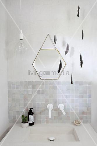 Mobile aus Federn und sechseckiger Spiegel überm Waschbecken
