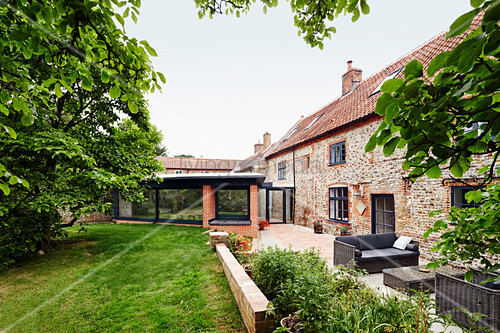View of extension and existing brick and flint farmhouse