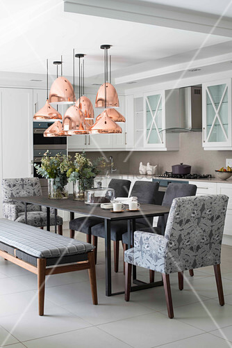 Copper ceiling lamps above dining table in kitchen-dining room