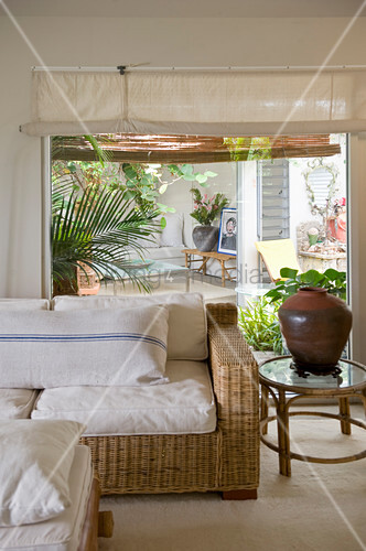 Wicker sofa in front of window with view onto summery terrace