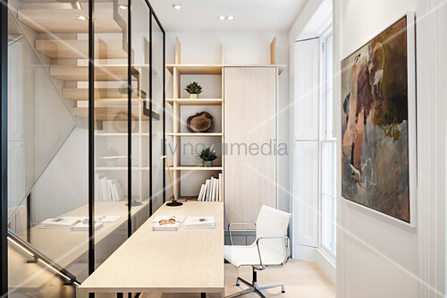 Schreibtisch im schmalen Arbeitszimmer mit Glaswand zur Treppe