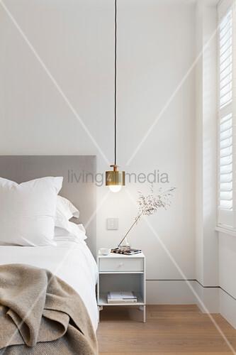 Goldene Pendelleuchte überm Nachttisch im Schlafzimmer