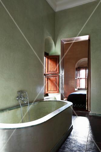 Masonry bathtub in Mediterranean bathroom with green walls