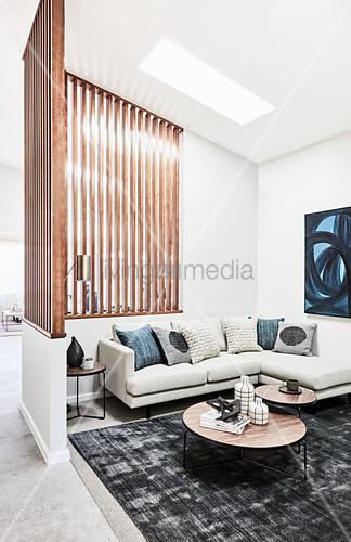 Helles Sofa übereck und Couchtsich-Set im Lounge-Bereich mit Holzlamellen