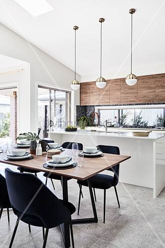 Set dining table, elegant chairs and kitchen island in open-plan interior