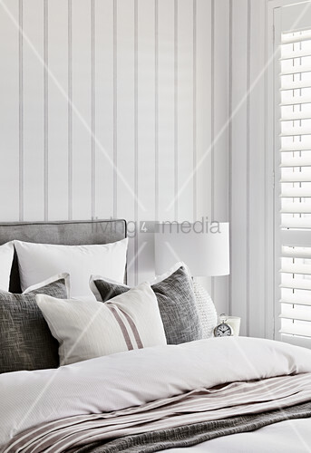 Scatter cushions on double bed in bedroom with white wood-clad walls