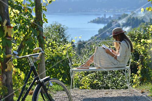 Frau mit Buch auf Bank sitzend, Blick auf See