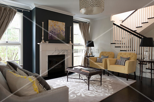 Pastel armchairs and coffee table in living room with black-painted chimney breast and staircase in background