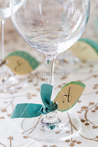 Handmade, leaf-shaped paper tags with initials tied to glasses